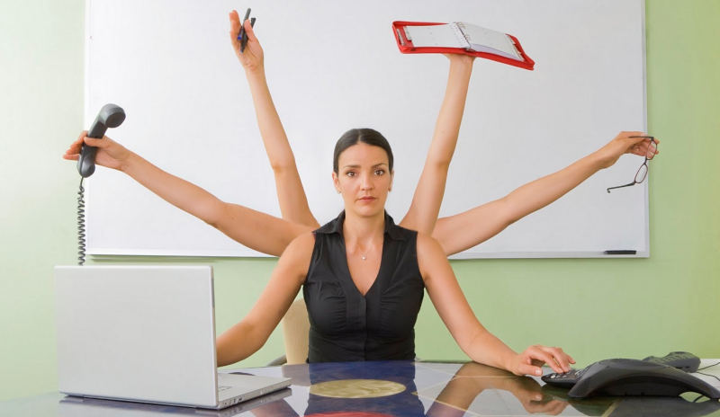 Woman sitting at a desk with 6 arms multitasking